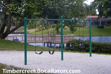 relax and enjoy a view of the lake at Timbercreek while your kids play on the swings.
